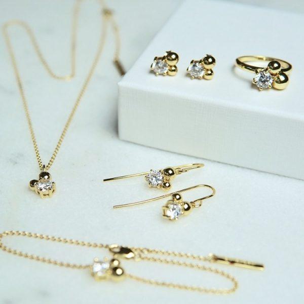 guldring med två guldkulor och sten