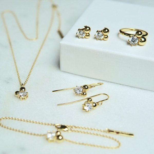 armband i guld med vit sten och guldkulor
